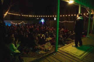 A man dressed in black with a white hoodie stands on an elevated porch serving as a stage illuminated in green light and tells his story to a crowd of about 100 people seated cozily on blankets on the ground in a backyard. Audience members at left clap. Fiesta style lights hang in the air over the audience