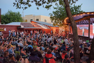 a crowd of about 100 people seated in foldable chairs and oriented toward the Scoot Inn's outdoor stage, where a blond woman in bright clothes tells a story