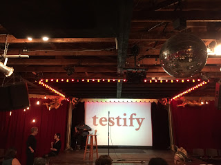 "Two female sign language interpreters dressed in black sign to each other. To the right of the interpreters is an elevated stage on which a man plays acoustic guitar. Also on stage is an empty stool and a microphone stand. Behind the stage the word ""testify"" in black text is projected over a white screen. Red curtains cover the walls on either side of the stage. A disco ball hangs in the foreground"