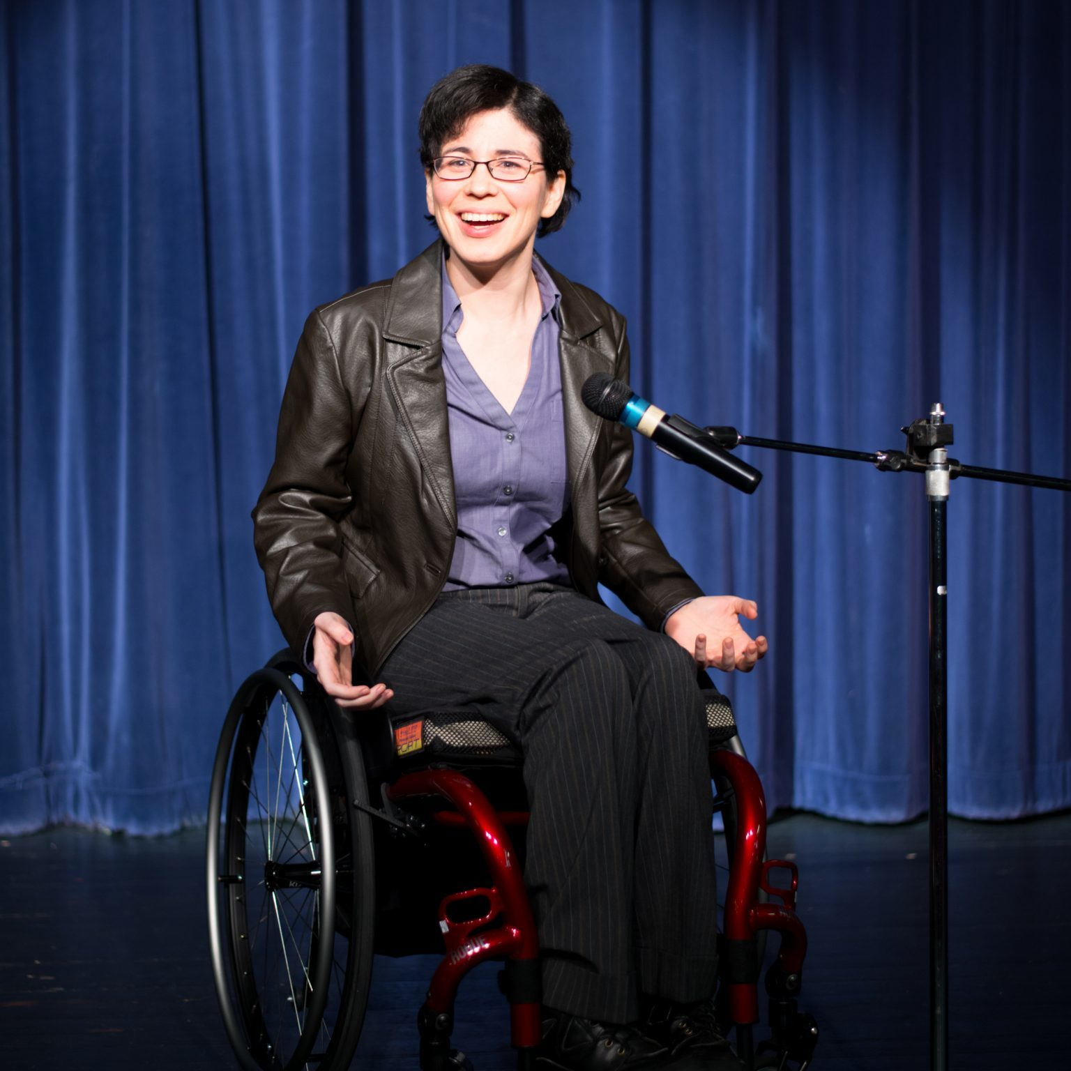 woman in a wheelchair at a microphone